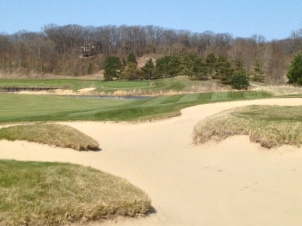 #10 - From the right fairway bunkers, with the green benched into the hill over water